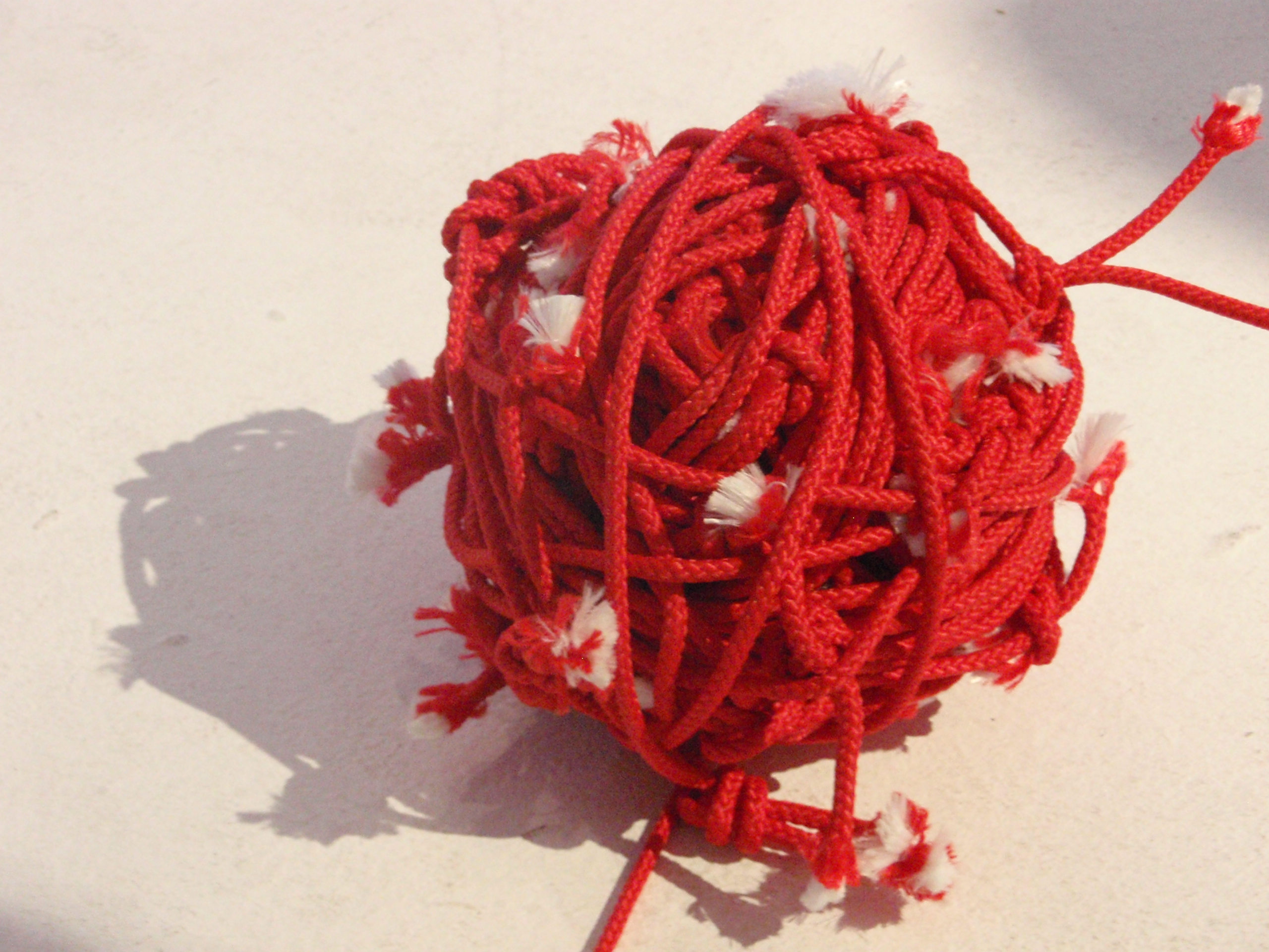Red ball of tangled threads